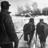 Sleigh Driver Standing Behind His Horses  Being Pulled Through the Deep Snow
