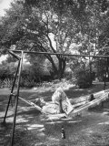 Man Laying in a Hammock with a Beer Beside Him
