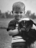 Little Boy Holding His New Friend  a Skunk