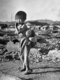 Girl Standing in Rubble from the Korean Civil War  Carrying a Baby in a Sling on Her Back