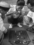 Boys Playing Board Game on Sidewalk in Front of the Trocadero Hotel