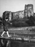 Boy Walking over a Narrow Spit of Land in River in Front of an Old Castle