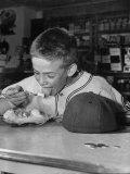 Boy Wearing Baseball Uniform Eating Banana Split at Soda Fountain Counter