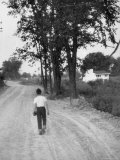 Boy Walking Home After Baseball Practice Along a Dirt Road