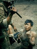 Bayonet Wielding South Vietnamese Soldier Menacing Captured Viet Cong Suspect During Interrogation