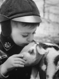 Little Boy Playing with Piglet on Farm in Kansas