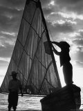 Fisherman Untying the Sail as the Sun Sets over the Water