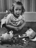 Little Girl Leaning over Her Broken Piggy Bank