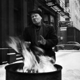 Old Man on Snowy City Street Warming Hands over Fire in Trash Barrel