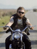 Member of Hell&#39;s Angels Riding Motorcycle on Road