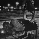 Weary Workman Resting Head on Steel Helmet While Lying on Bench