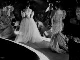 Socialites Wearing Elaborate Evening Dresses and Parading Across Stage During Charity Fashion Show