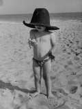 Little Boy at the Beach Wearing a Oversized Cowboy Hat Playing with a Toy Pistol