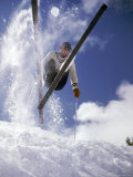 Skier Kicking Up Powder as He Jumps over Hill