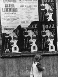 Child Walking Past Posters Advertising Jazz Festival