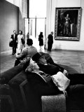 Two Weary American Tourists Resting on Sofa in Gallery of the Louvre