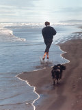 Presidential Candidate Bobby Kennedy and His Dog, Freckles, Running on Beach Papier Photo par Bill Eppridge