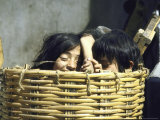 Two Children Playing in Straw Basket at Local Market
