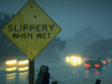Slippery When Wet Sign in Fore with Traffic in Background in Rain on California Highway 14