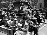 Woman Knitting Among Lunchtime Loungers Relaxing at Base of Statue at New York Public Library