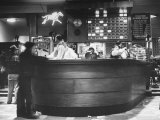 Men Placing Bets on Horses at the Casino Counter