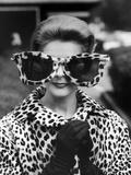La mannequin June Pickney portant un manteau de fourrure en léopard et d'énormes lunettes de soleil bordées de fourrure de léopard Papier Photo par Stan Wayman
