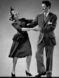 Model Wearing Afternoon Dress and Feathered Hat Dancing with Man Wearing Sport Jacket
