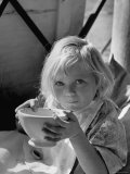Young Orphan Girl Drinking from Bowl at Table