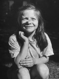 Young Girl with Long Hair and Raggedy Shirt  Smiling  Wearing Seed Pod on Nose