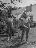Teenage Twin Girls Hanging Laundry on Clothesline