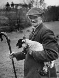 Shepherd Holding a Four Day Old Lamb While Holding a Cane in the Other Hand