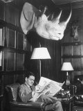Member Reading Newspaper in Smoking Room at the Harvard Club Beneath a Rhino Head Trophy