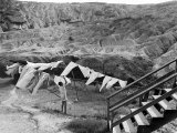 Woman Hanging Laundry with Land Erosion in the Background
