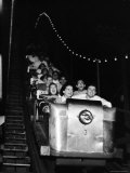 Teenagers in Rollercoaster at Night