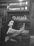 "Young Woman Wearing a Winter Coat and Hat  Reading Beneath ""D 6th Avenue"" Sign  Riding the Subway"