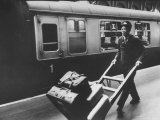 Railroad Porter Pushing Hand Truck Loaded with Baggage Past Passenger Car at Railroad Platform