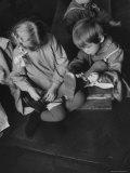 Older Girl Helping Younger Tie Shoe in Russian Kindergarten