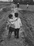Vietnamese Farm People Walking on Raised Path Between Rice Paddies