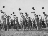 Women's Gym Class with Rows of Women Throwing Balls Into Air in Unison