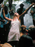 Young Woman with Flute Ecstatically Raising Her Arms  Amid Crowd at Woodstock Music Festival