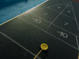Setting up for a Shot on a Shuffleboard Game on a Cruise Ship