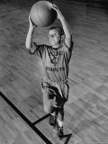Young Boy Wearing School Gym Clothes Hooting a Basket Ball from the Free-throw Line