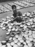 Young Merchant Drying Out Trays Full of Opened Coconuts in His Yard