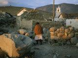 An Aymara Woman and Cat on a Path in an Atacama Desert Village