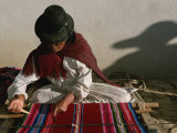 A Bolivian Woman Weaves Brightly Colored Fabric on a Loom