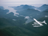 A Beaver Airplane on Floats Flies over Islands and Snowy Mountains