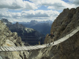 A Man Walking Across a Bridge in the Dolemites  Cortina  Italy