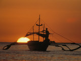 A Man and an Outrigger Silhouetted against a Brilliant Orange Sky