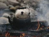 A Kettle of Water Comes to a Boil over a Smoky Campfire