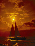 A Passing Sailboat is Silhouetted against a Brilliant Orange Sunset Near Bermuda